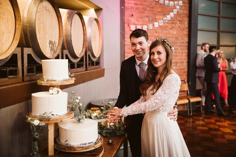 Bride in Emma Beaumont Wedding Dress with Long Sleeves Cutting the Wedding Cake