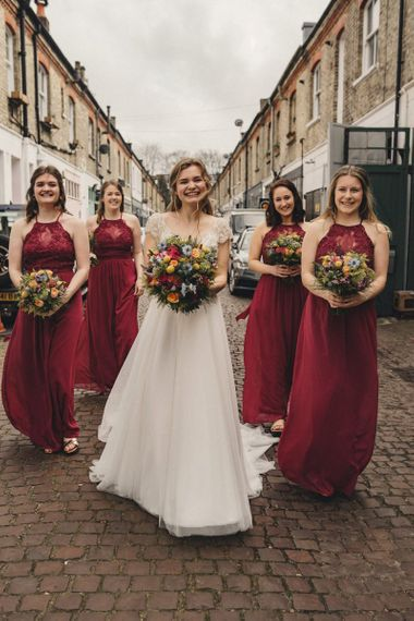 Bridal party portrait with bridesmaids in red dress holding colourful bouquets