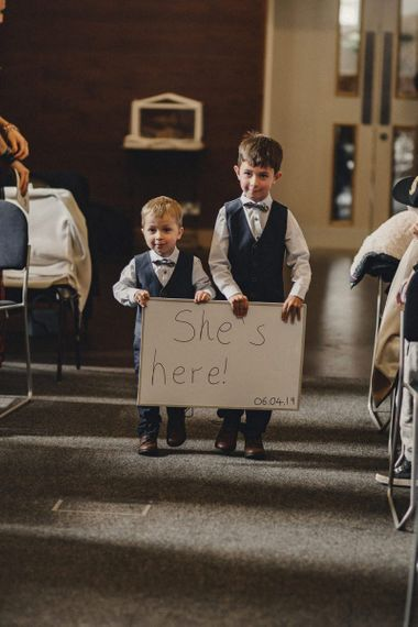 page boys with 'She's Here' sign