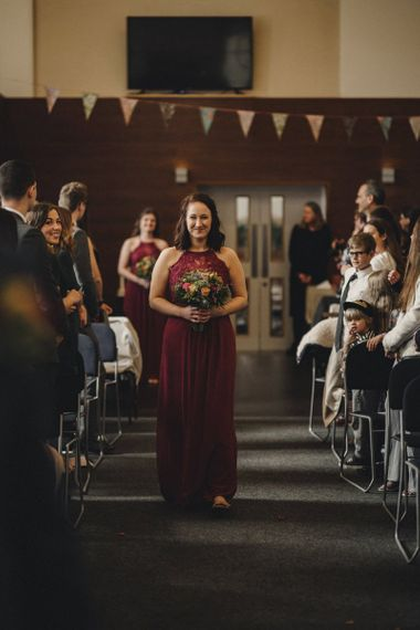 Bridesmaid in red halterneck dress walking down the aisle
