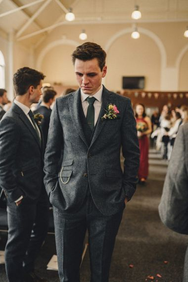 Emotional groom in blue wool suit waiting for his bride to arrive