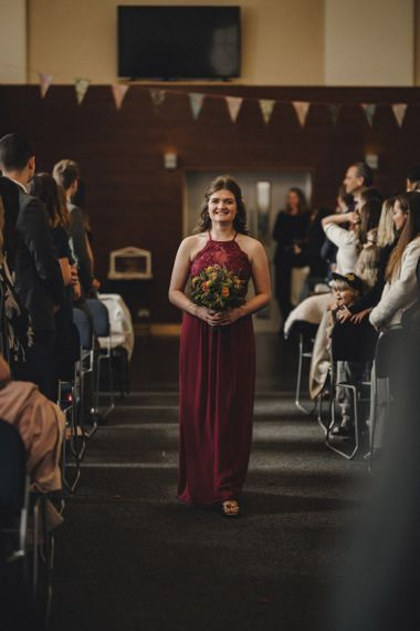 Bridesmaid in red dress walking down the aisle