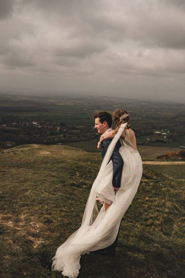 bride on her grooms back in the countryside