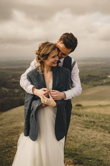 groom wrapping his bride in a jacket to keep her warm