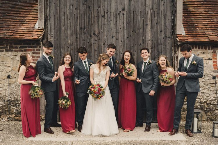wedding party portrait with bridesmaids in red dresses and groomsmen in dark blue wool suits