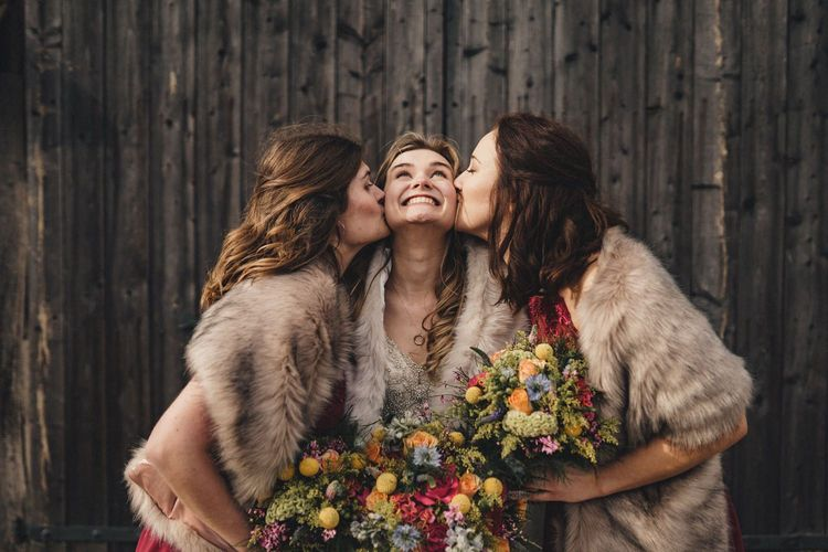bride with her bridesmaids kissing her cheeks