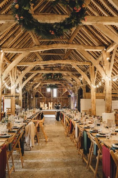 Rustic barn wedding reception with string lights and colourful flowers