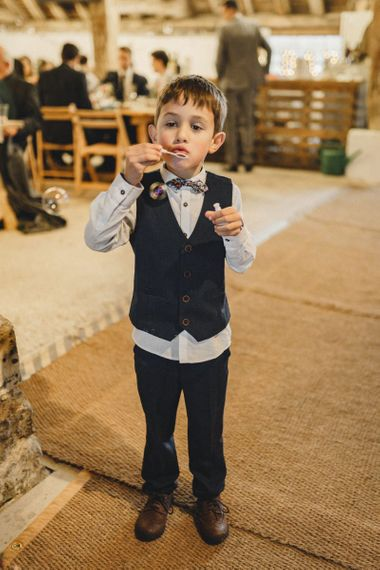 Page boy blowing bubbles at rustic wedding