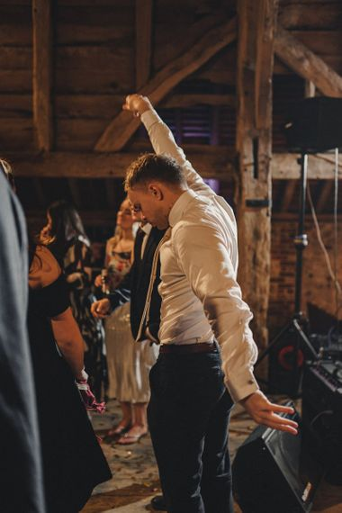 Wedding guests dancing at the rustic barn evening reception