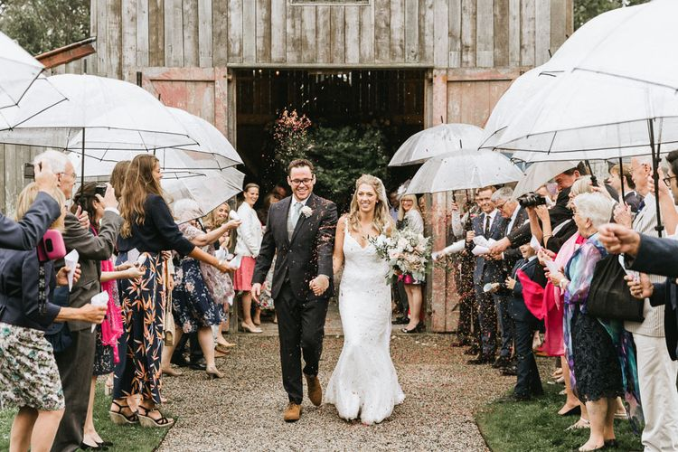 Confetti exit for bride and groom during travel themed wedding