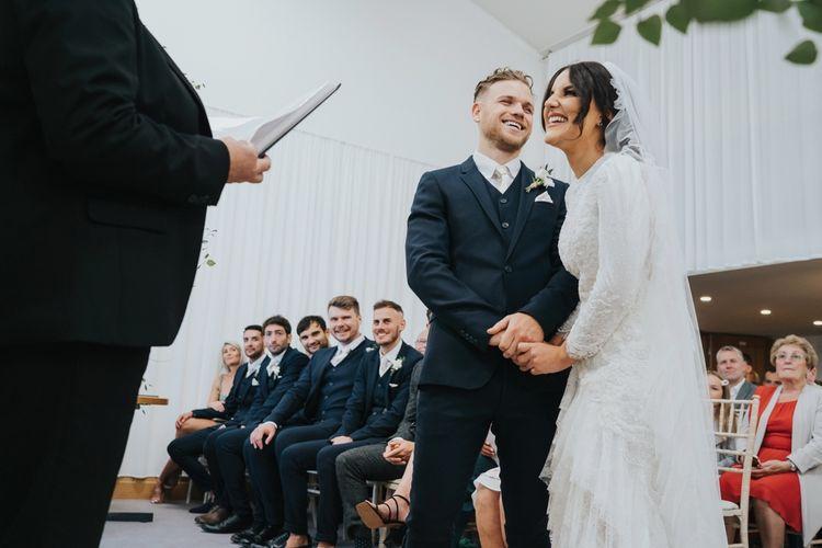 Bride in bespoke Emma Beaumont wedding dress with ruffle hem veil