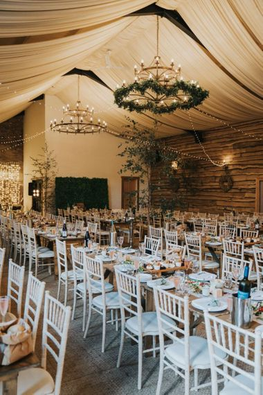 Wedding breakfast decor with foliage chandelier and fairy light backdrop