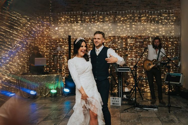 Bride and groom dance in front of fairy light backdrop