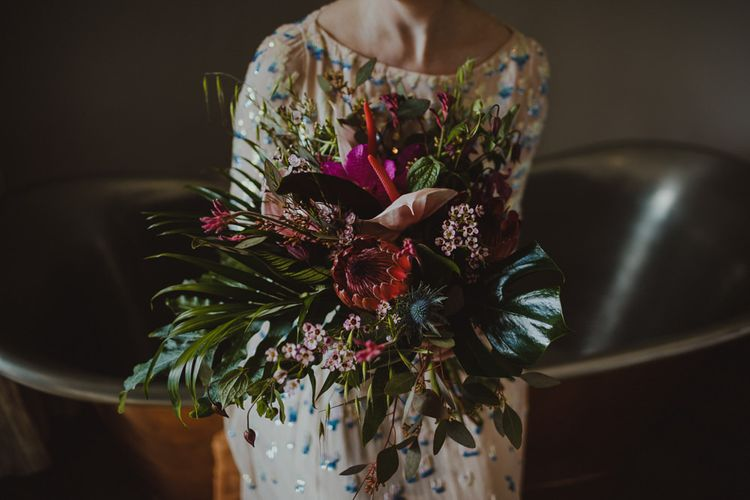 Bride wearing embellished dress and botanical bouquet with pink orchids & king proteas