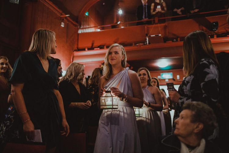 Bridesmaids wearing wrap dress and candle lanterns at Sheffield wedding with theatre ceremony