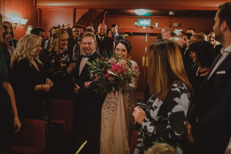 Bride walking down the aisle at Sheffield wedding with theatre ceremony wearing embellished dress and botanical bouquet