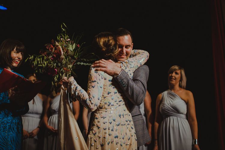 Bride and groom embrace on stage at Sheffield wedding wearing embellished dress and botanical bouquet of orchids & king proteas