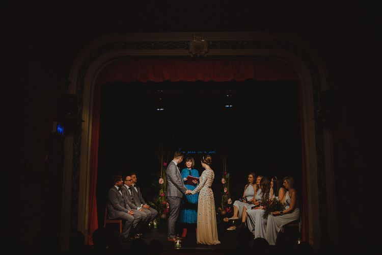 Bride and groom tie the knot on stage with bridesmaids wearing wrap dresses at Sheffield wedding with theatre ceremony