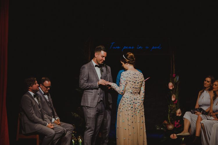 Bride and groom tie the knot on stage wearing embellished bridal dress at Sheffield wedding with theatre ceremony