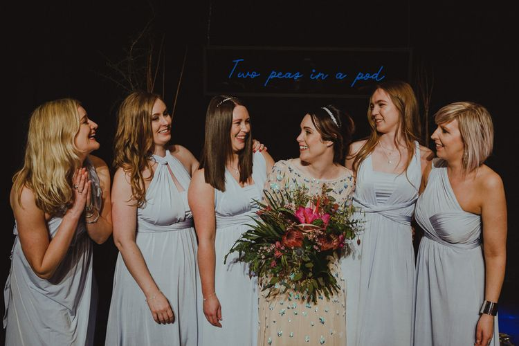 Bridesmaids wearing blue wrap style dresses with the bride in embellished bridal dress and pink botanical bouquet
