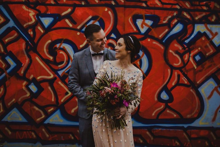 Bride and groom embrace at Sheffield wedding with industrial styling and a pink botanical bouquet