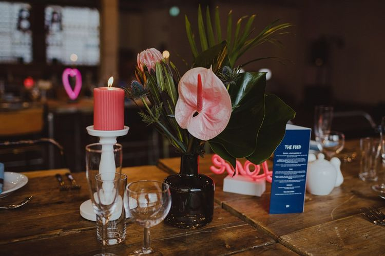 Pink pillar candles with neon signs and botanical floral arrangements for disco industrial reception