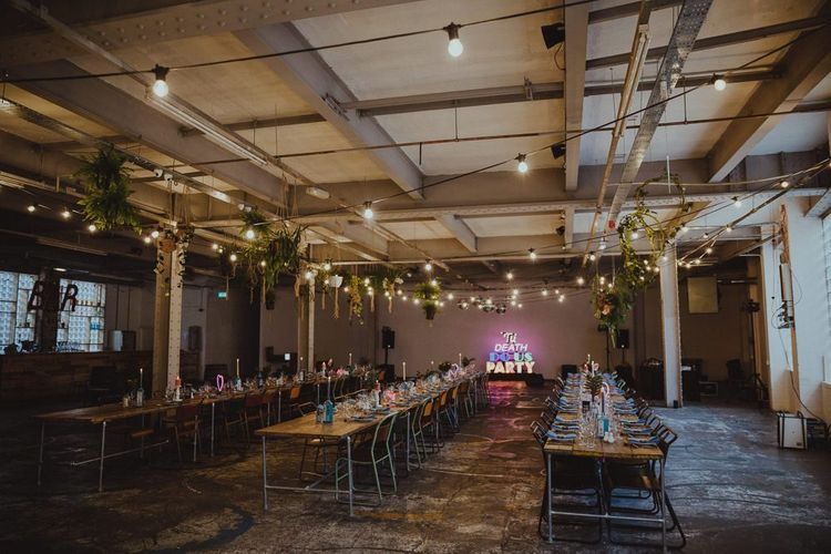 Festoon lighting and tropical flowers at Sheffield wedding with industrial reception