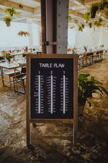 Chalkboard table plan at industrial reception with disco rave theme at tropical floral decor