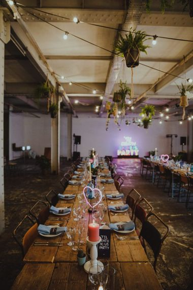 Neon light signs at industrial reception with disco rave theme and hanging tropical floral decor