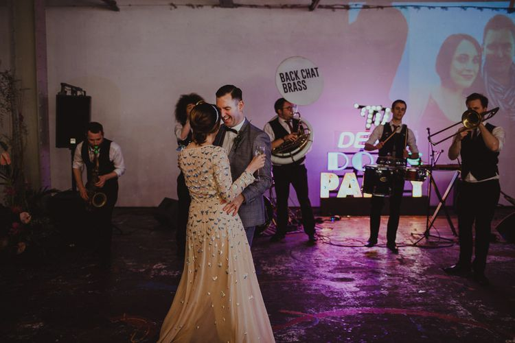 Bride and groom dance to brass band with disco ball decor at disco rave reception with 'Til death do us party' neon sign