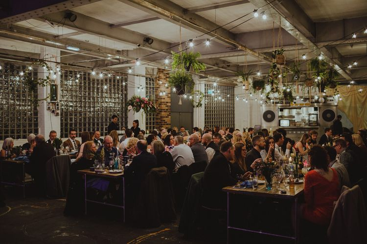 Industrial style warehouse reception with hanging tropical decor and festoon lighting at Sheffield wedding