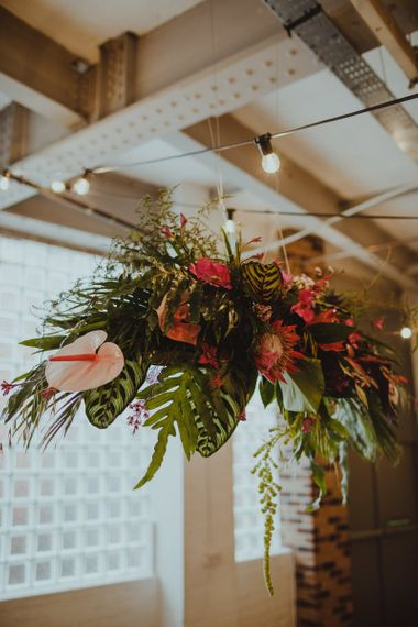 Hanging tropical floral decor with pink anthuriums, orchids and fern leaves