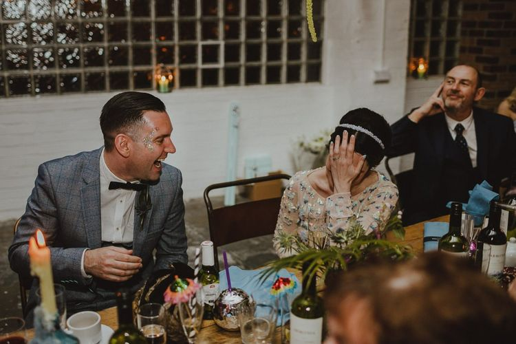 Bride and groom enjoying the speeches at Sheffield wedding with disco rave reception wearing a sequin embellished bridal dress and headband