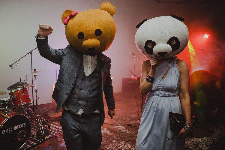 Groom and bridesmaid wearing bear head props from the Photo Booth at disco rave reception