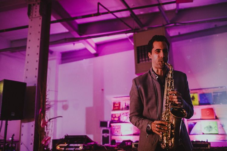 Saxaphonist at industrial styled disco rave reception with neon lights