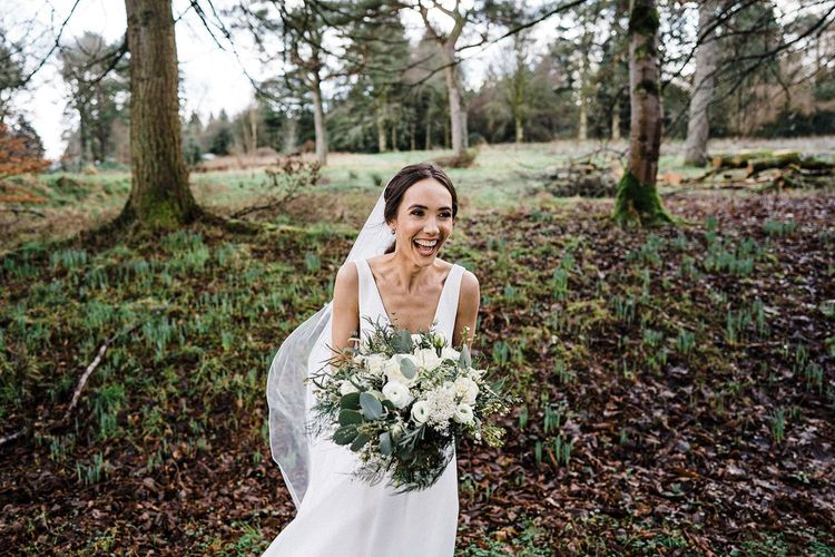 Bride in Suzanne Neville wedding dress with large white bouquet