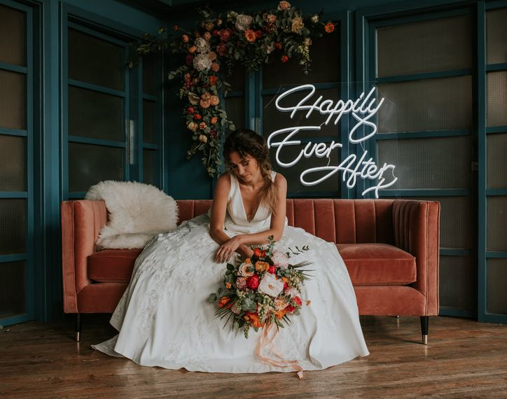 Bride Sitting on Velvet Sofa with Neon 'Happily Ever After ' Sign Backdrop
