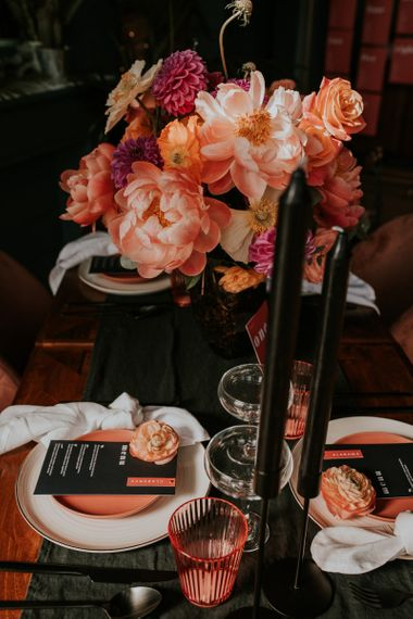 Black Table Runner and Taper Candles against Living Coral Flowers and Tableware