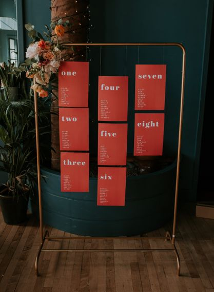 Copper Frame Table Plan with Statement Table Stationery Hanging From it Decorated with Flowers