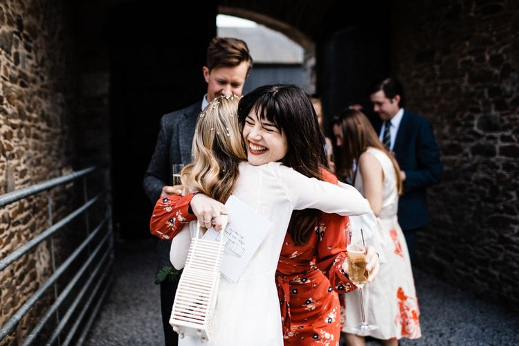 Stylish Wedding Guest in Red Floral Dress and Bangs Hugging The Bride