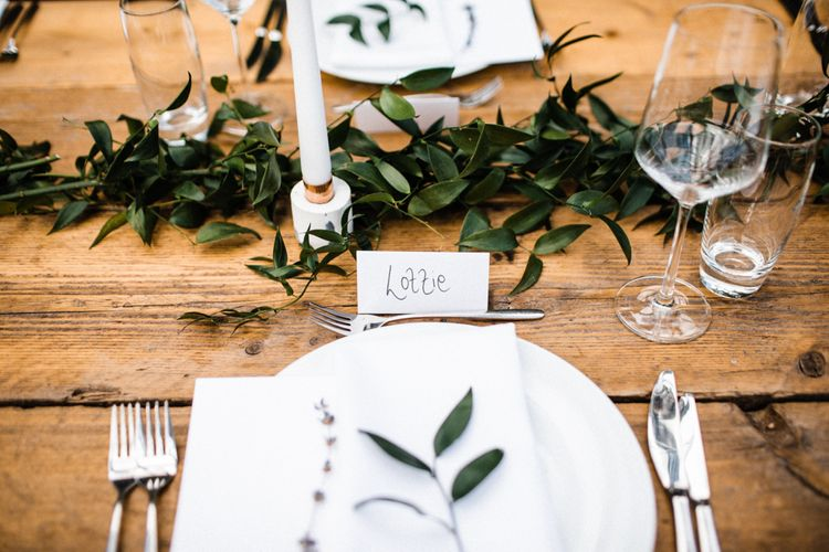 Place Setting with Greenery Runner and White Candles