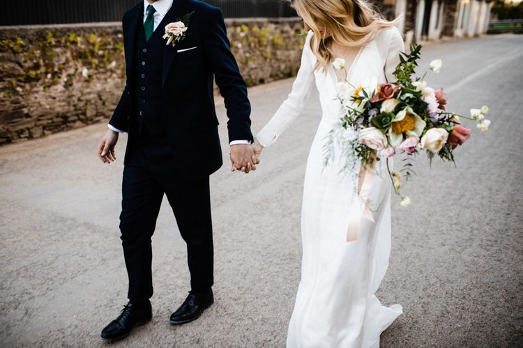 Bride in Andrea Hawkes Wedding Dress and Groom in Navy Suit Holding Hands