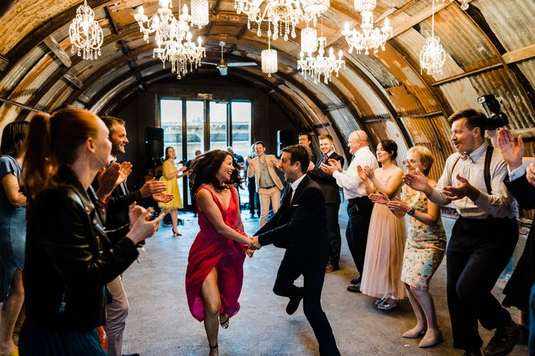 Wedding Guests Dancing Under a Ceiling of Chandeliers