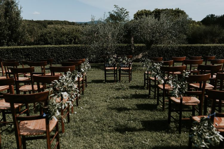 Aisle and Altar Chairs Decorated with Foliage Wedding Flowers