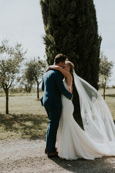 Bride in Sottero & Midgley Wedding Dress  and Groom in Three-piece Navy Wedding Suit Kissing at First Look Moment