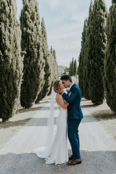 Bride in Sottero & Midgley Wedding Dress  and Groom in Three-piece Navy Wedding Suit Kissing