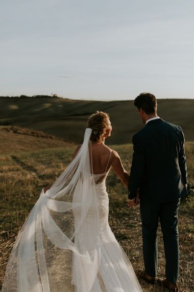 Beautiful Bride in Sottero & Midgley Wedding Dress and Groom in Navy Suit Walking Through the Tuscan Hills