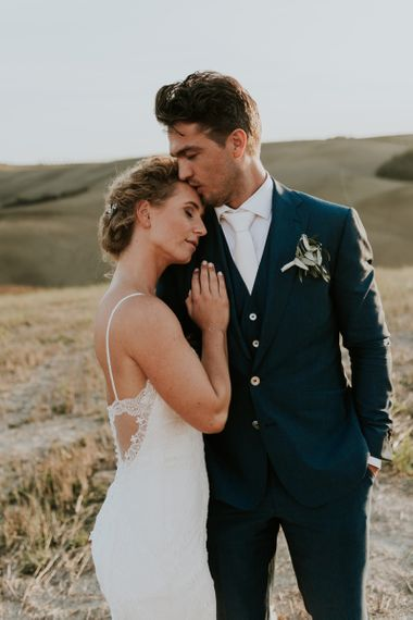 Groom in Navy Suit and White Tie Hugging Bride in Lace  Sottero & Midgley Wedding Dress with Spaghetti Straps