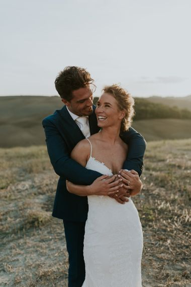 Groom in Navy Suit and White Tie Embracing Bride in Lace  Sottero & Midgley Wedding Dress in the Tuscan Hills