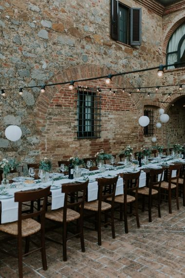 Outdoor Tuscan Wedding Reception Decor with Festoon Lights and Greenery Centrepieces